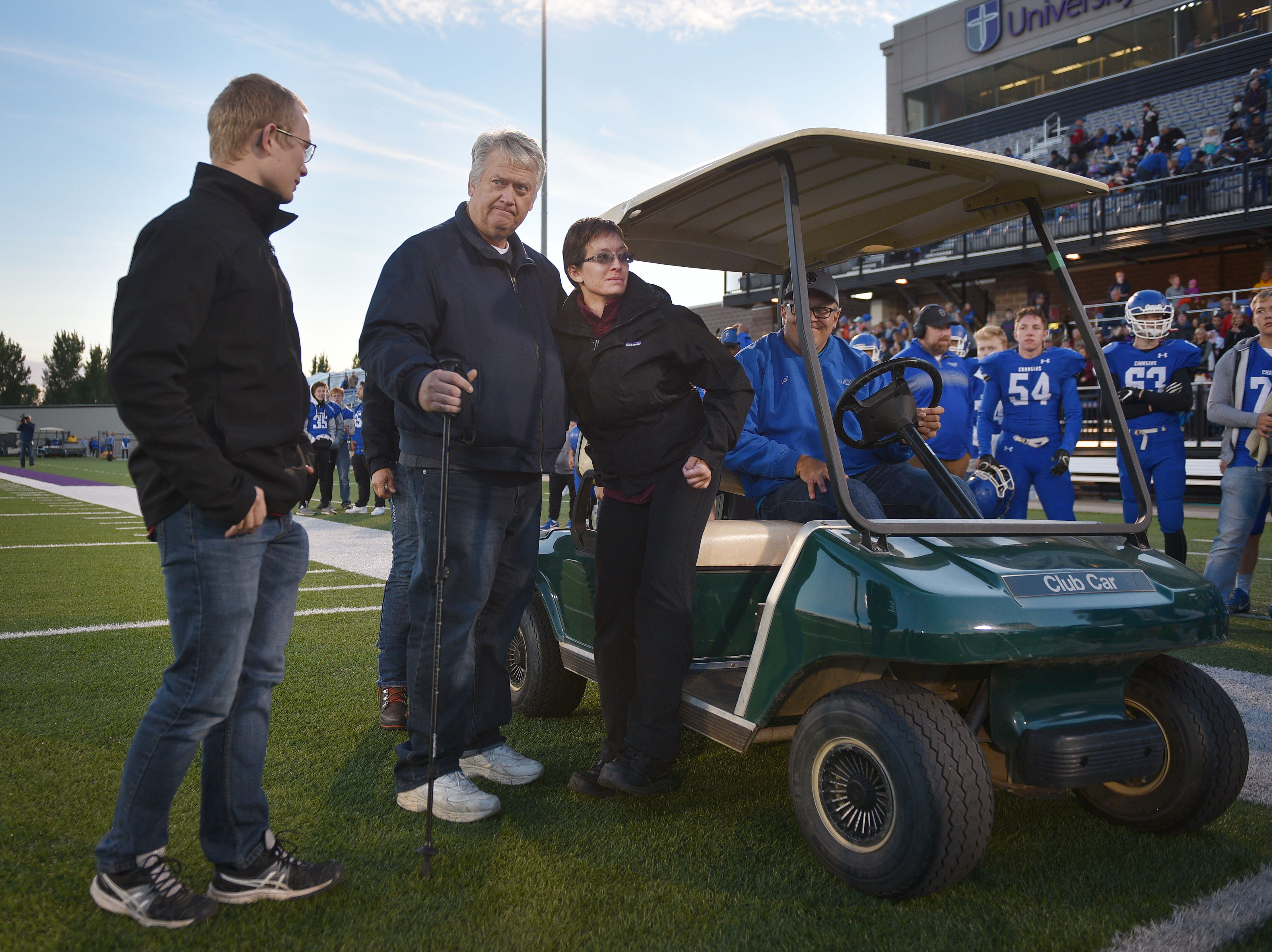 Ashley's dad Lyle Van Hemert and her brother Caleb, left, help Ashley off the field after the coin toss, Friday Sept. 28, at Bob Young Field University Of Sioux Falls Stadium.
