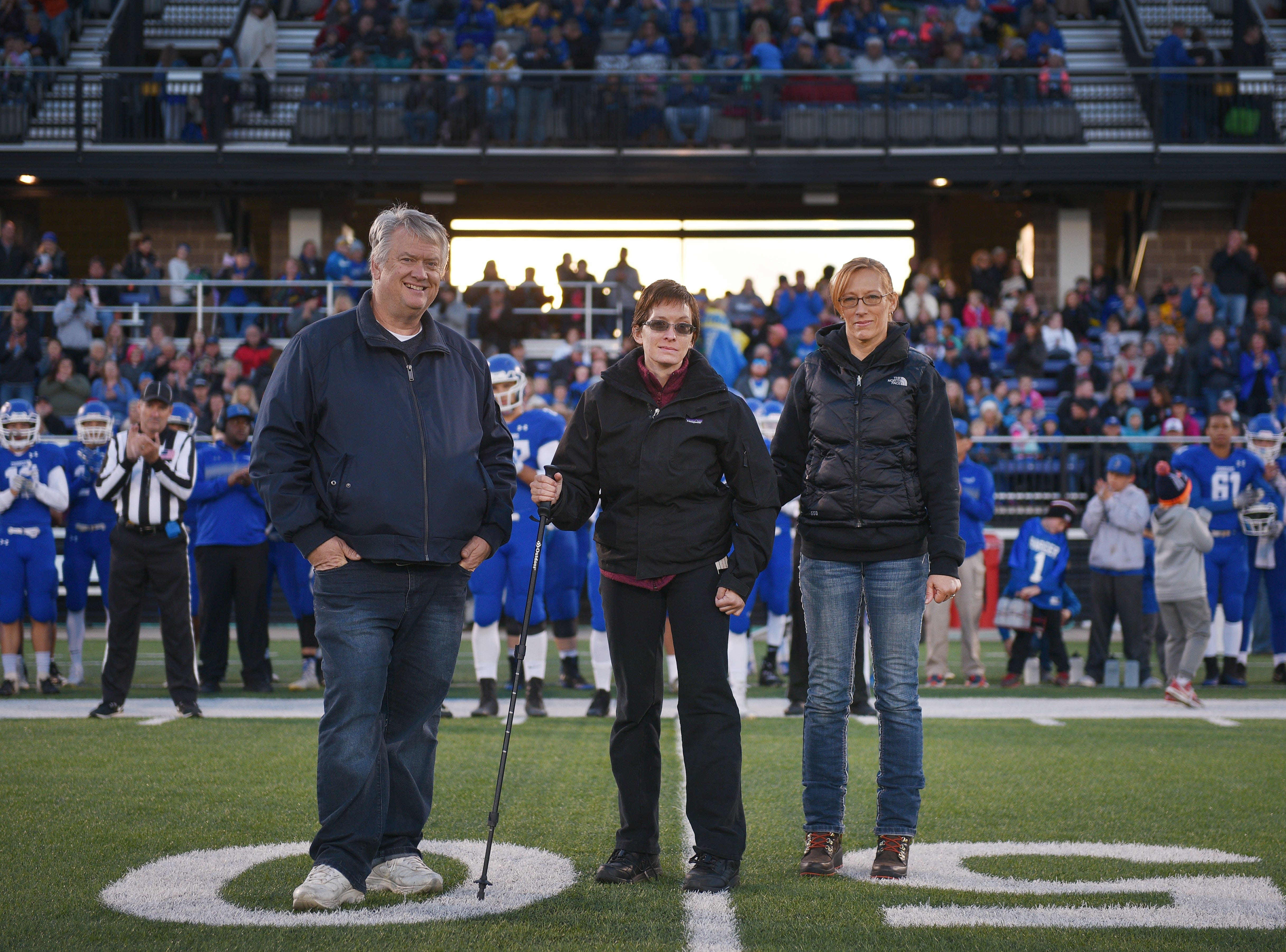 Ashley Van Hemert and her parents Linda and Lyle stand on the 50 yard line for the coin toss before the Sioux Falls Christian game, Friday Sept. 28, at Bob Young Field University Of Sioux Falls Stadium.