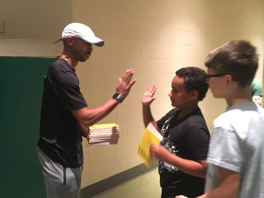 """Wilson Middle School student Keishawn Dayal gives a high-five to Stanley Peyton Jr. Friday after receiving his copy of the book, """"Ghost."""" Parker Baucom watches as he waits to get his book."""