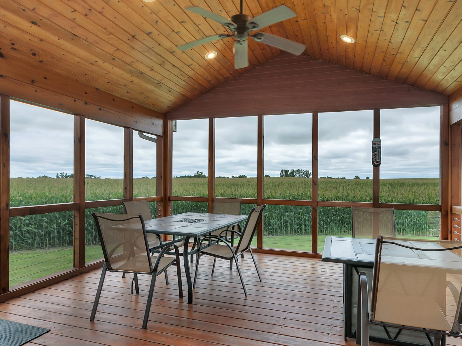 Off the kitchen and the dining room is a comfortable fully screened-in porch likely to be one of the most used spaces in the home three out of the four seasons of the year.
