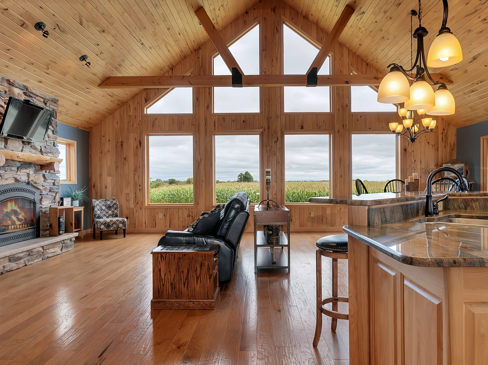 The main floor living room is part of a great space filled with perfect touches: from the hand-scraped hickory floors all the way up to the vaulted wood ceiling, from the beautiful stone fireplace to the picturesque view of corn swaying in the breeze.