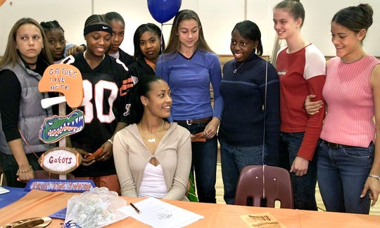 Dalila Eshe, center, of Florida High School sits surrounded by her teammates after signing a letter of intent to play basketball at the University of Florida Wednesday morning.