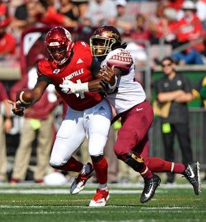 Louisville Cardinals quarterback Jawon Pass (4) recovers his own fumble under the pressure of Florida State Seminoles linebacker DeCalon Brooks (28) during first quarter at Cardinal Stadium.