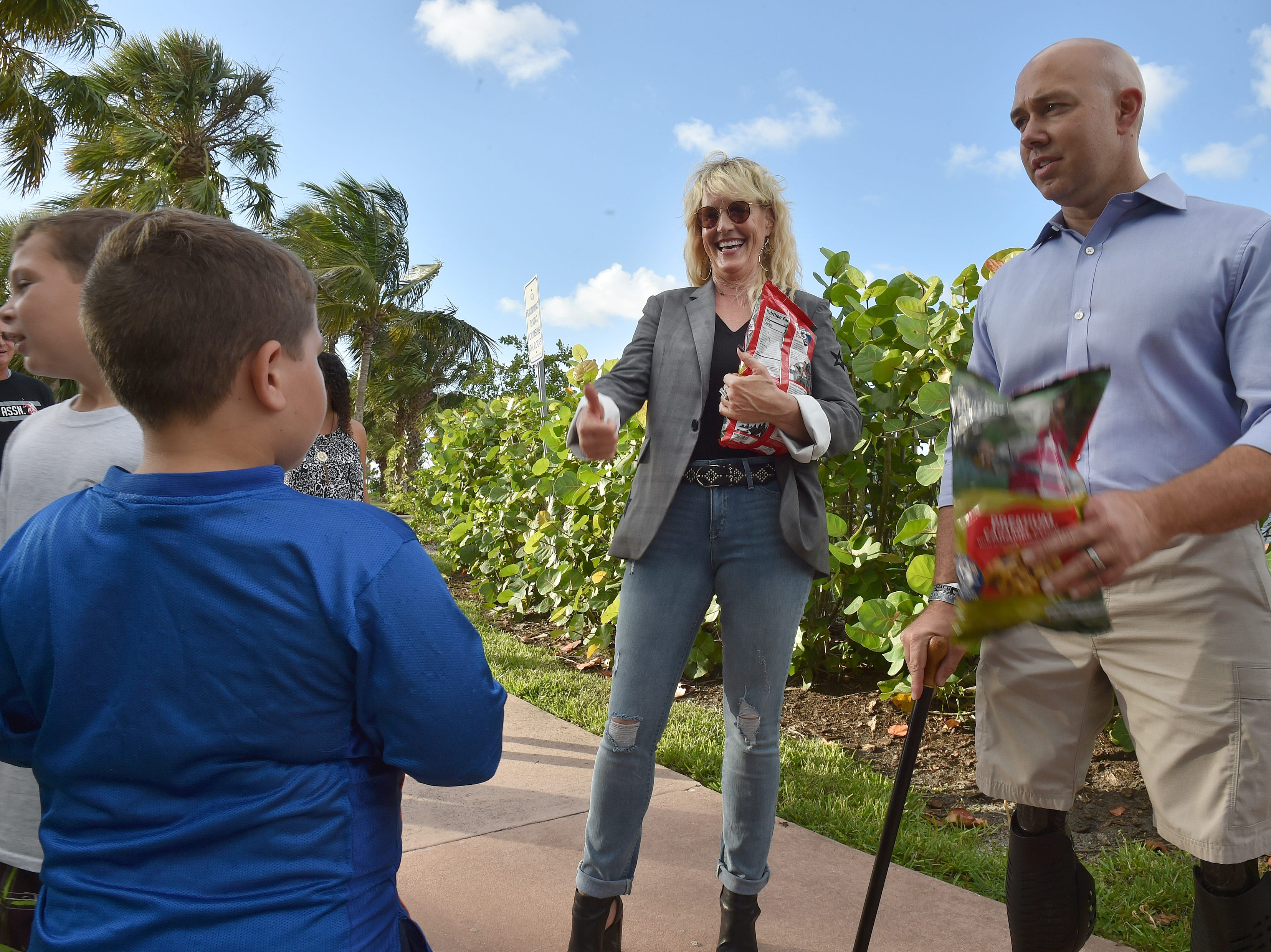 Environmentalist activist Erin Brockovich gestures to Zacharyah Buys, 8 (in blue), of  Jensen Beach after he and his brother Zasha, 10, spoke with Brockovich and U.S. Congressman Brian Mast at Flagler Park on Sunday, September 30, 2018 in Stuart.  Brockovich and Congressman Mast spoke to a crowd at the park, advocating for clean water in Stuart.