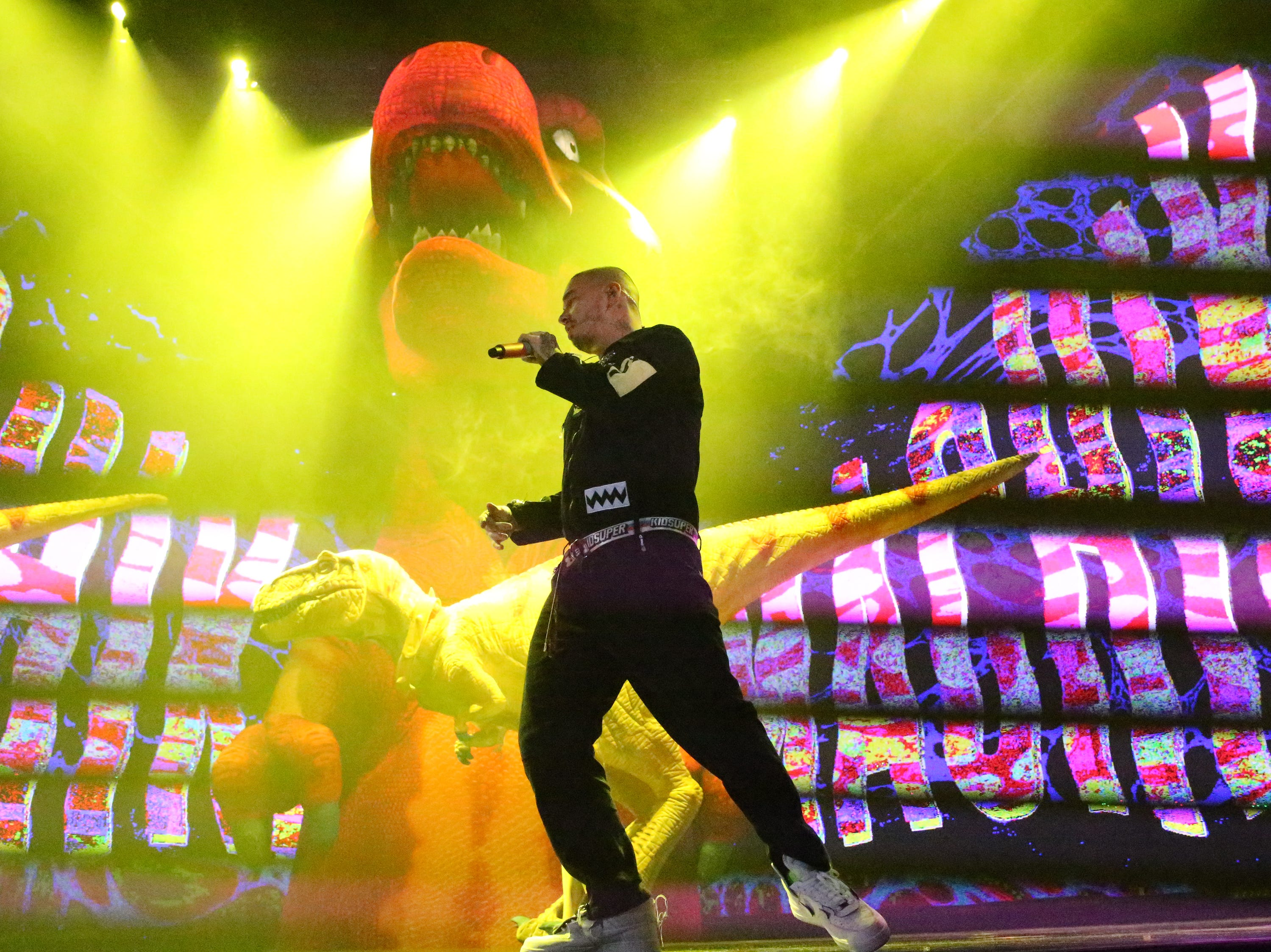 Reggaeton singer J Balvin is surrounded by dinosaurs on stage during his Sunday night show at the Don Haskins Center.