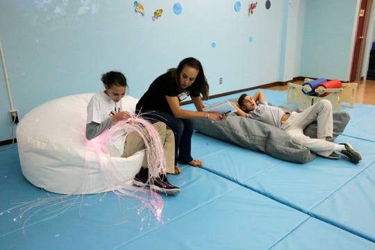 Natalia Oronoz, an Evaluator for the El Paso Independent School District shares a moment with a Lincoln Middle School student using the sensory room at the school.