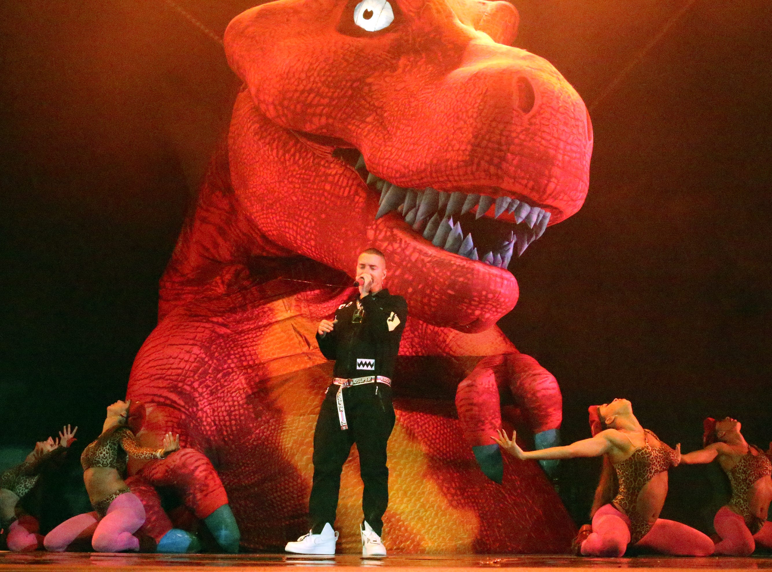 Reggaeton singer J Balvin is surrounded by dinosaurs and dancers on stage during his Sunday night show at the Don Haskins Center.