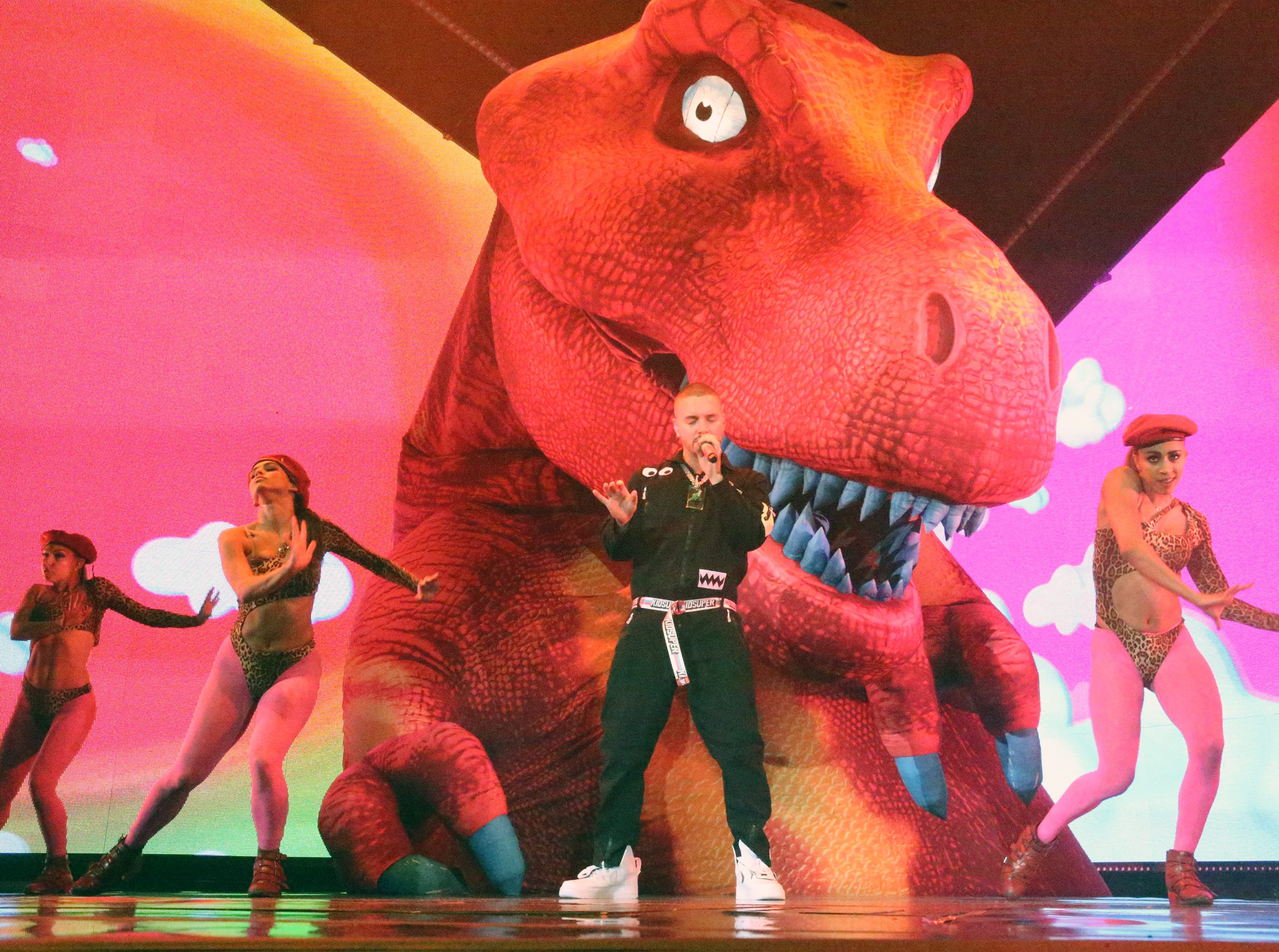 Singer J Balvin is joined on stage by dancers and a giant dinosaur looming above him Sunday night in the Don Haskins Center.