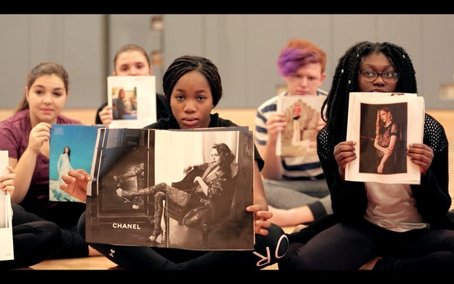 """In this shot from the movie, """"Straight/Curve: Redefining Body Image,"""" students at Trevor Day High School in Manhattan hold up magazine images of what they think they """"should"""" look like. The movie will be shown at Oxnard College and Thursday, and the filmmaker will hold a question-and-answer session afterward."""