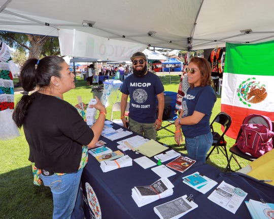 Booths at the Oxnard Multicultural Festival represent nonprofit organizations as well as countries. Here, Edgar Vicente and Norma Gomez staff a booth for the Mixteco/Indigena Community Organizing Project.