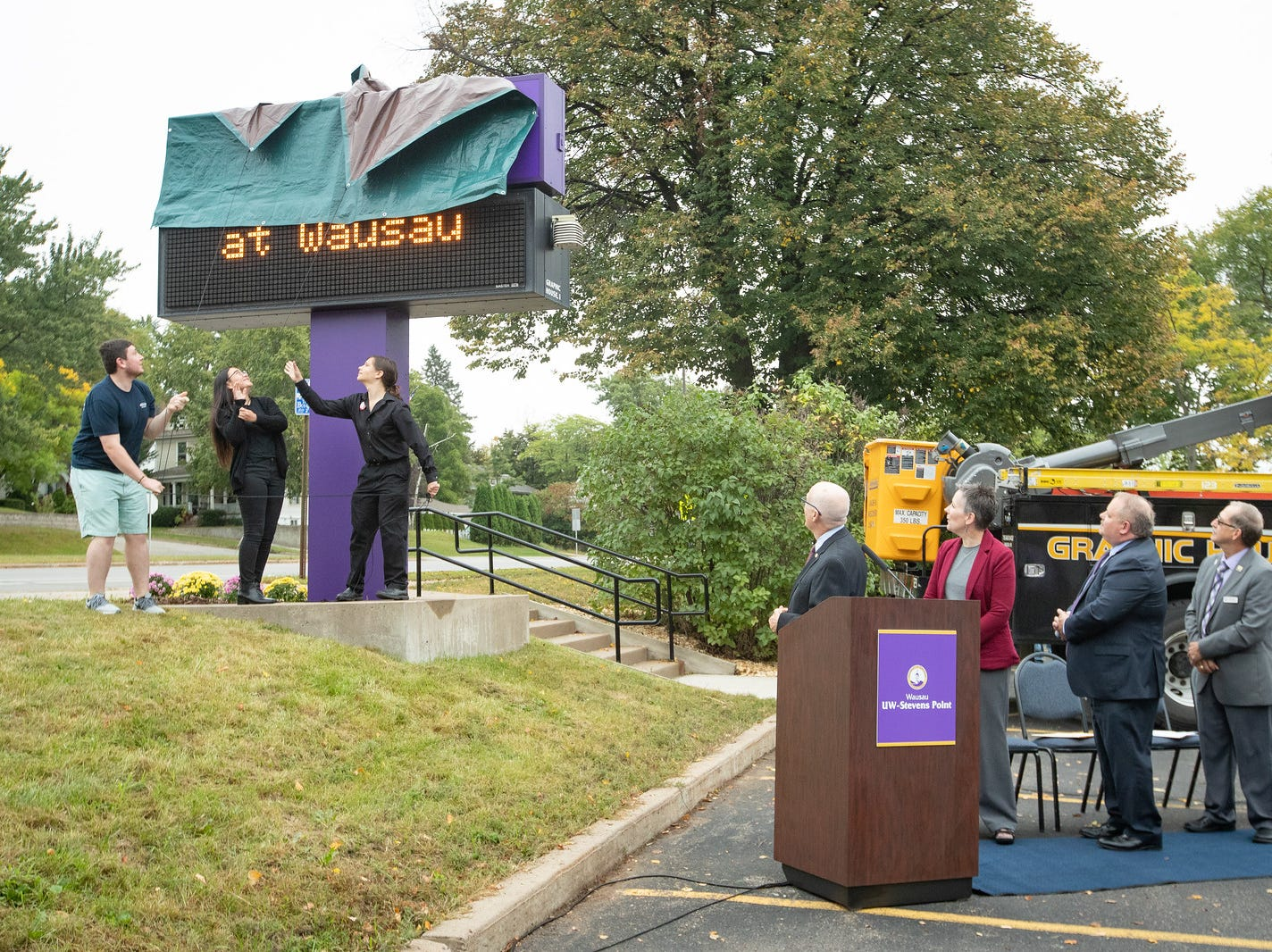 University of Wisconsin-Stevens Point at Wausau students Christian Bump, Cassandra Xiong and Grace Stolen unveil a new campus sign Sept. 19 on the former University of Wisconsin Marathon County campus.