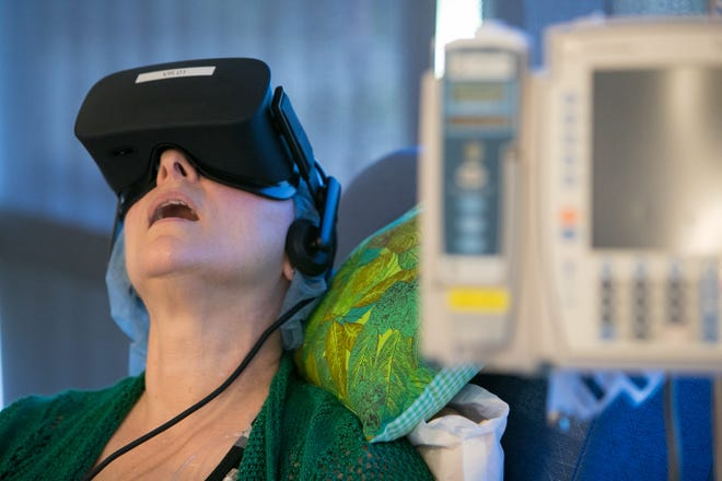 Cancer patient Kathleen Krakowski puts on the Oculus Rift virtual reality headset for the first time as she experiences the sites and sounds of a forest.