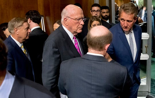 Sen. Jeff Flake, R-Ariz., right, speaks with Patrick Leahy, D-Vt., third from right, and Sen. Chris Coons, D-Del., second from right, at the conclusion of a Senate Judiciary Committee hearing on Capitol Hill in Washington, Friday, Sept. 28, 2018, after Flake calls for an FBI investigation into the allegations brought forward against Supreme Court nominee Judge Brett Kavanaugh. The committee voted along party lines to send the Kavanaugh nomination to the full Senate for a vote. Also pictured is Sen. Lindsey Graham, R-S.C., left. (AP Photo/Andrew Harnik)