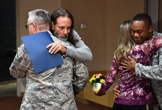 Vern and Bianka Landavazo give hugs to MSgt. Brion Kennedy, left, and Sgt. Anthony McCall of the 365th Training Squadron at Sheppard Air Force Base Monday morning. The squadron presented the couple with a weekend getaway gift. The murder trial for their daughter's killer wrapped up last month.
