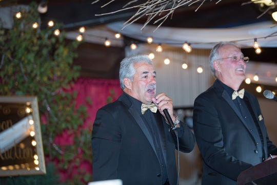 Jerry Meissner, left, prepares to auction an item at Marshfield Clinic Research Institute's National Farm Medicine Center's Auction of Champions with Louis Krainz. The annual event raised funds for farmer mental health and safety programs.