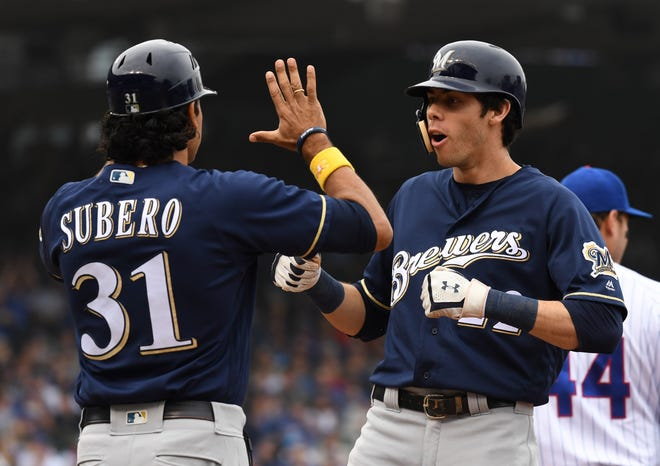 First base coach Carlos Subero and center fielder Christian Yelich celebrate his RBI single during the third inning against the Chicago Cubs in the National League Central division tiebreaker game at Wrigley Field.
