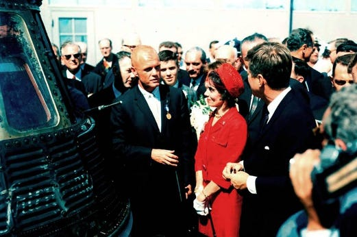 John Glenn, stands next to his Friendship 7 capsule in which he made his historic orbital flight, meets with President John F. Kennedy.  Mrs. Glenn stands next to her husband.  Earlier that day, President Kennedy presented the NASA Distinguished Service Award to Glenn.