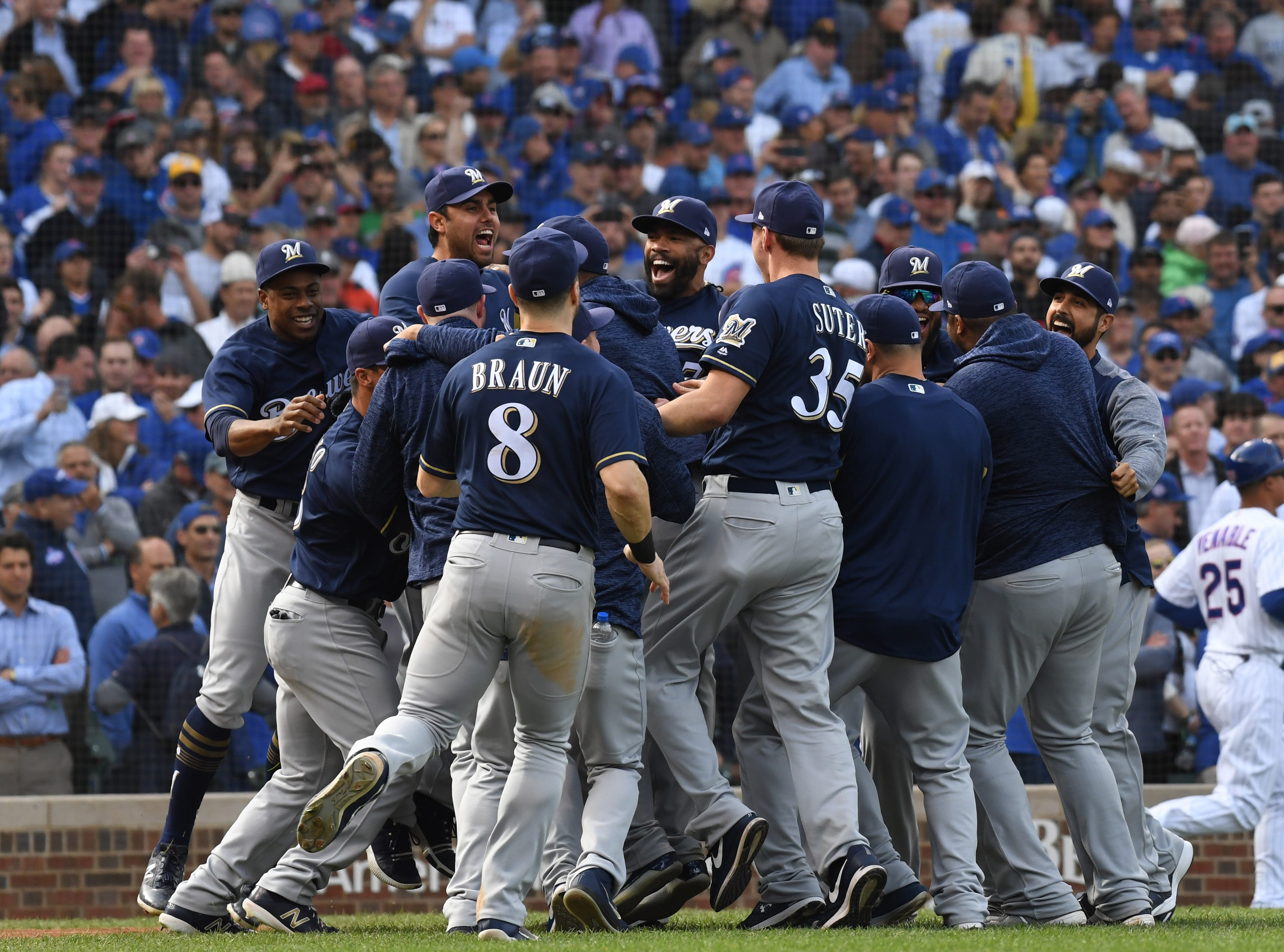 Brewers celebrate after the final out of the 3-1 win against the Cubs.