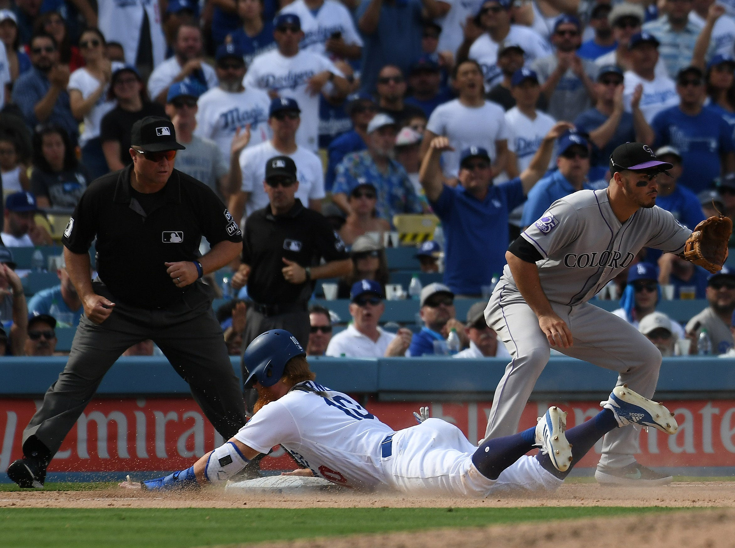 Dodgers third baseman Justin Turner slides safely into third base in the seventh inning.