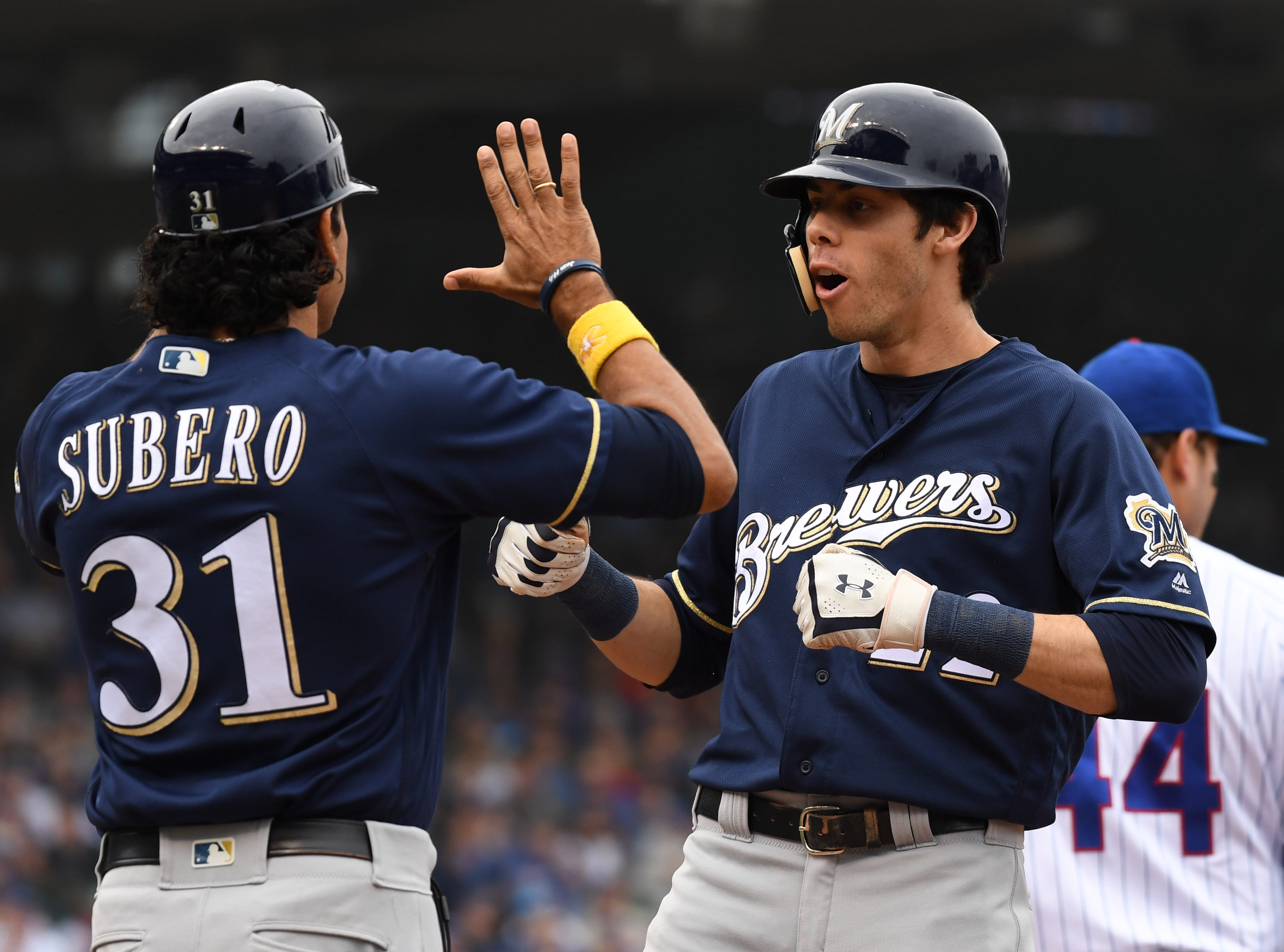 Brewers first base coach Carlos Subero  and outfielder Christian Yelich celebrate Yelich's RBI single in the third inning.