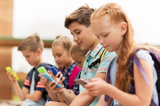 A group of kids check out their smartphones.