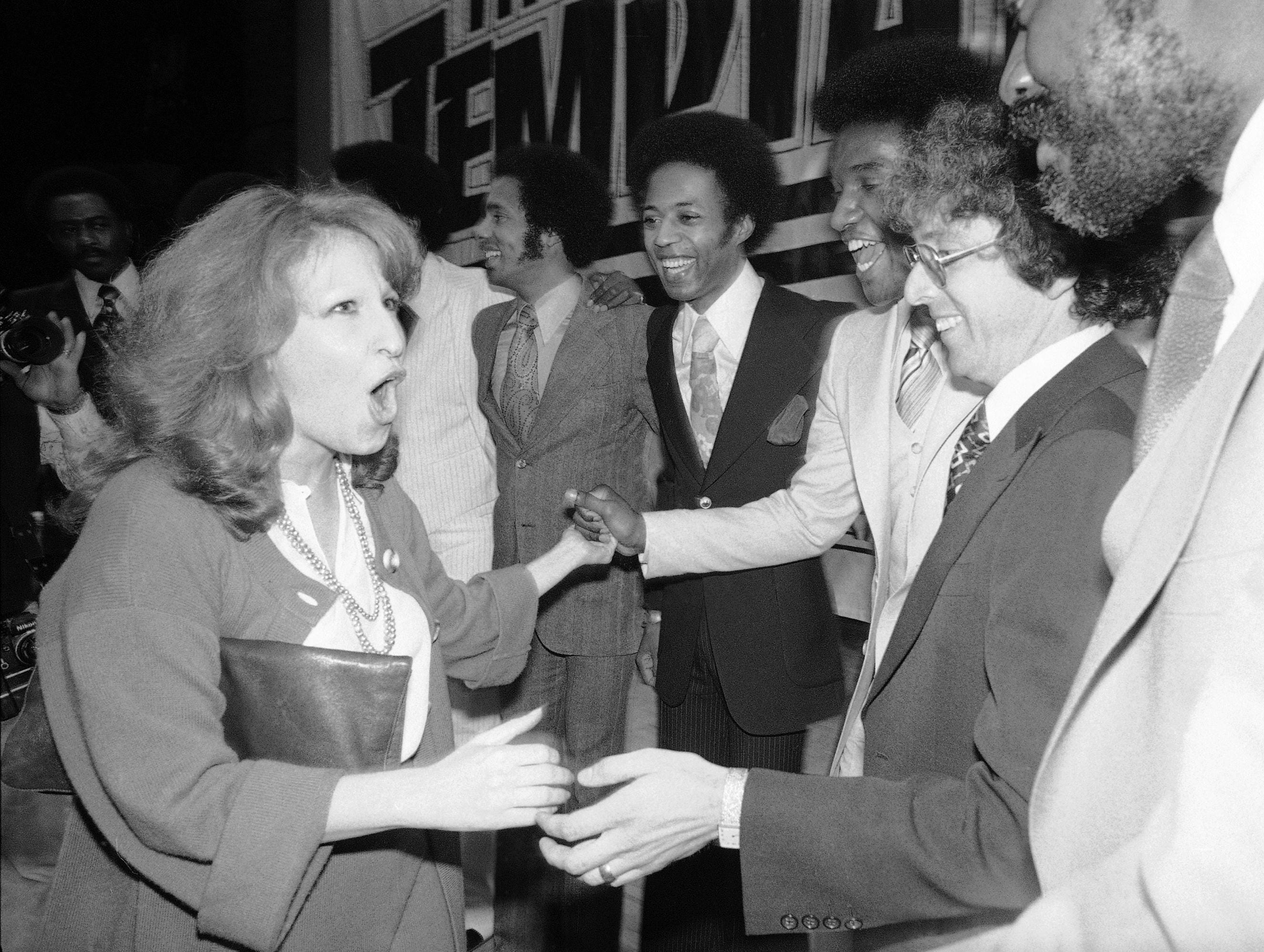 Bette Midler, left, greets members of the soul group, the Temptations and other guests at a party on May 9, 1977.
