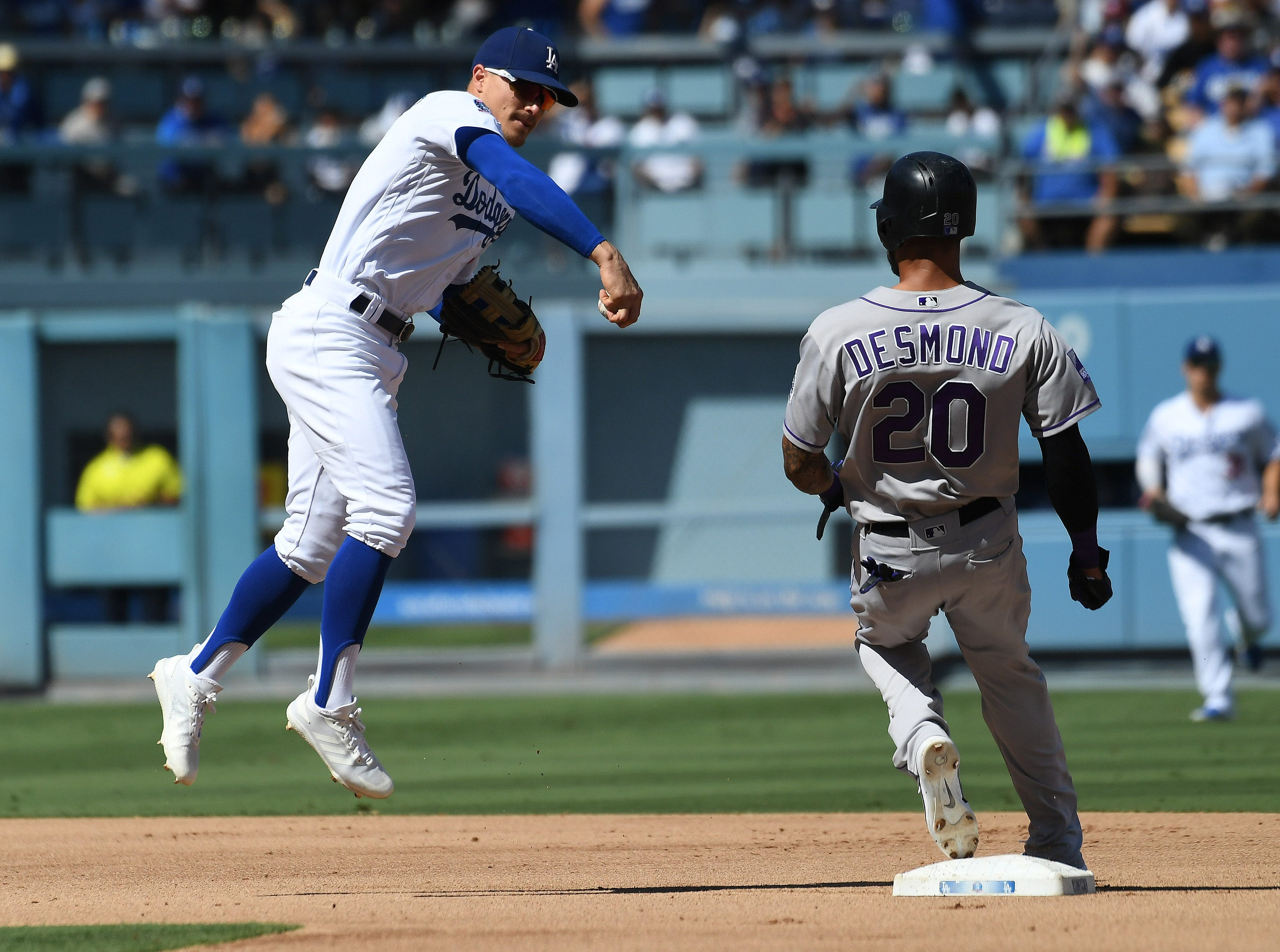 Colorado's Ian Desmond is out at second base as Dodgers infielder Kike Hernandez doesn't throw to first.