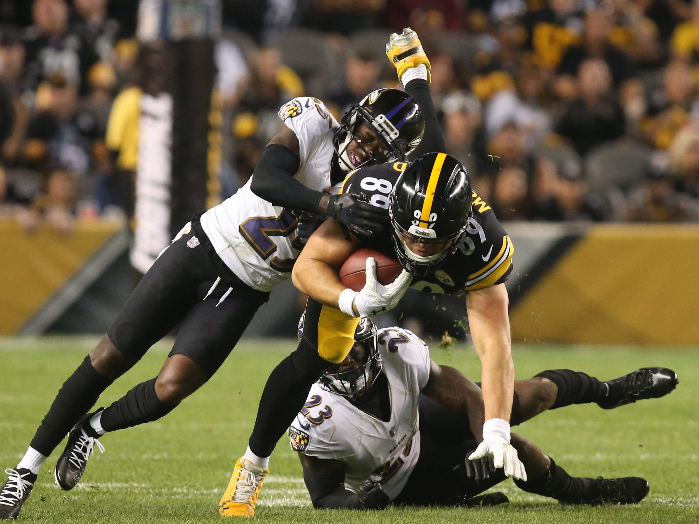 Pittsburgh Steelers tight end Vance McDonald runs after a catch as the Baltimore Ravens' Tavon Young (25) and  Tony Jefferson (23) tackle during the second quarter at Heinz Field.