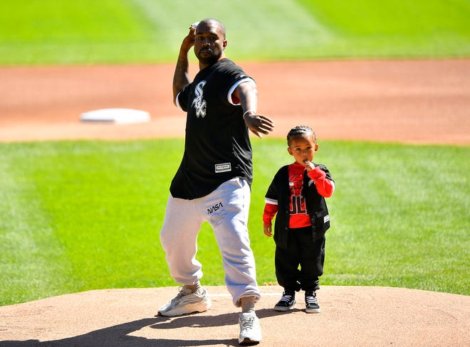 Kanye West and his son Saint throw out a ceremonial first pitch before the game between the Chicago White Sox and the Chicago Cubs.