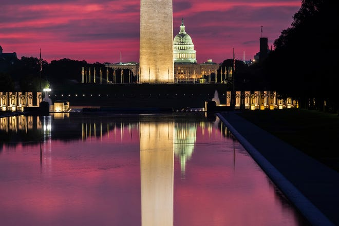 The U.S. Capitol and base of the Washington Monument are mirrored in the reflecting pool on the National Mall at sunrise in Washington, Aug. 25, 2018.