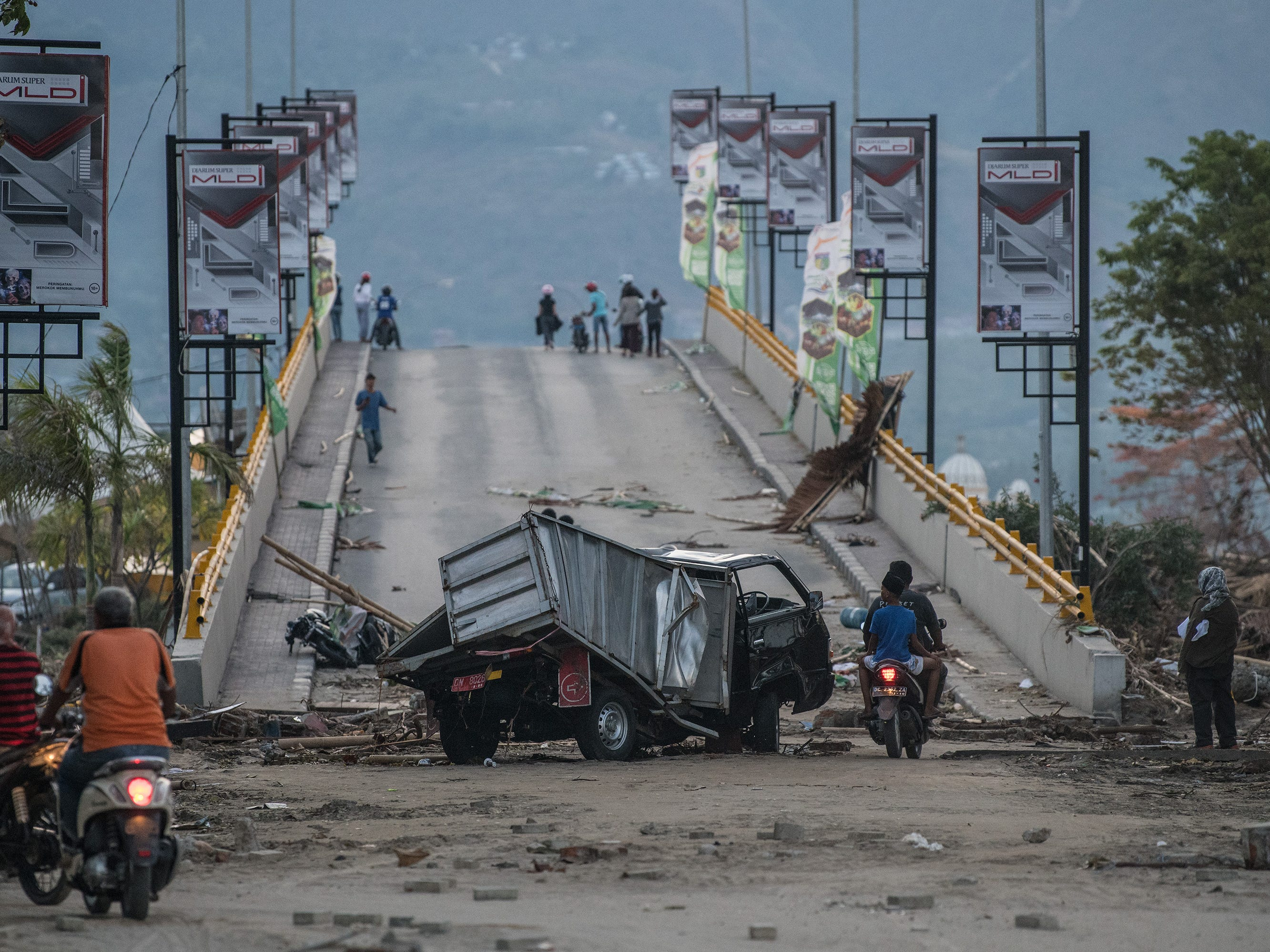 PALU, INDONESIA - OCTOBER 01: A smashed vehicle lies at the foot of a bridge that has been destroyed by a tsunami, on October 01, 2018 in Palu, Indonesia. Over 844 people have been confirmed dead after a tsunami triggered by a magnitude 7.5 earthquake slammed into Indonesia's coastline on the island of Sulawesi, causing thousands of homes to collapse, along with hospitals, hotels and shopping centers. Emergency services fear that the death toll could rise into the thousands as rescue teams made contact with the nearby cities of Donggala and Mamuju and strong aftershocks continue to rock the city.