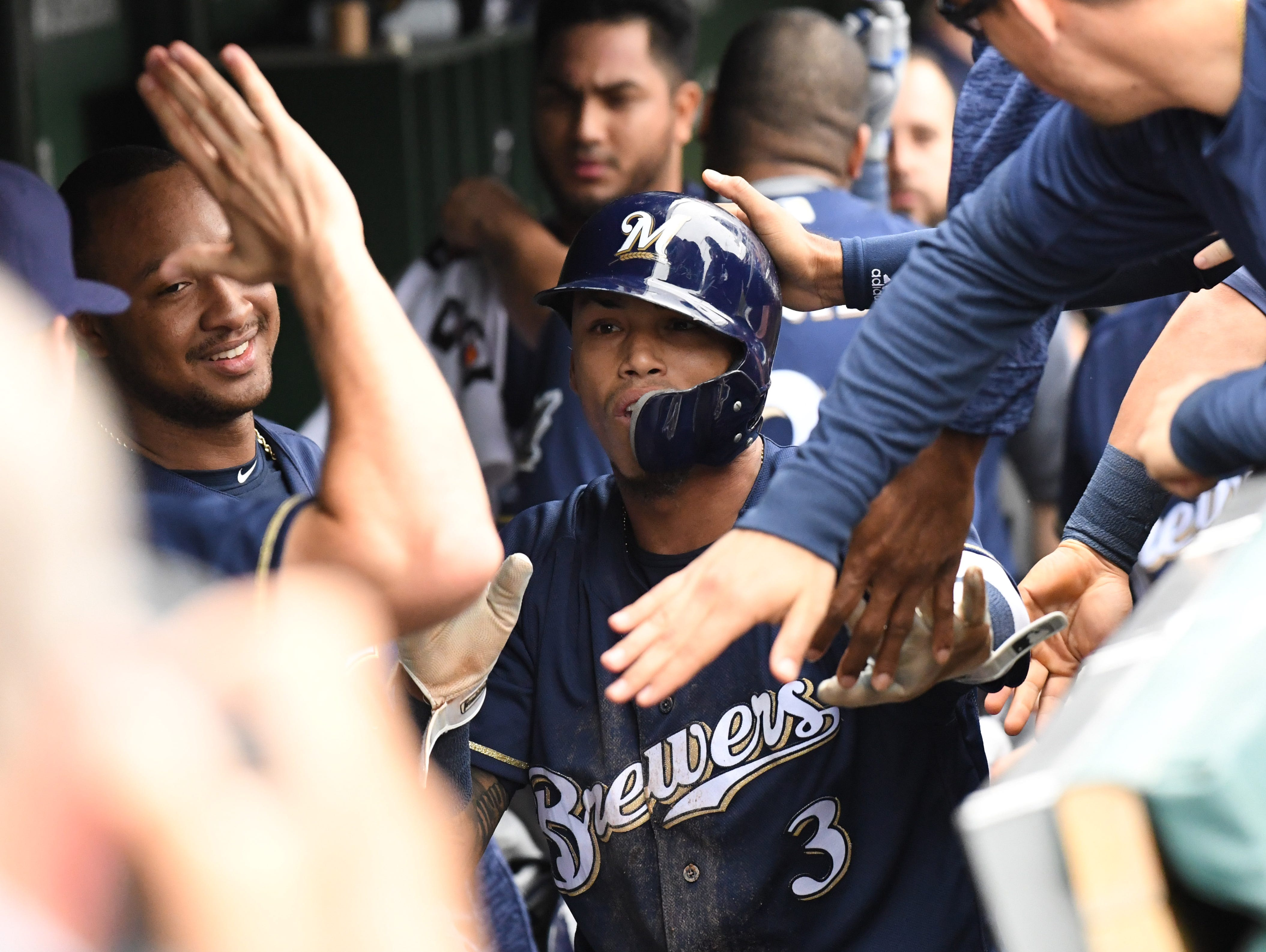 Brewers shortstop Orlando Arcia celebrates in the dugout after scoring in the third inning.