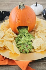 Halloween-themed guacamole 'barfing' pumpkin.
