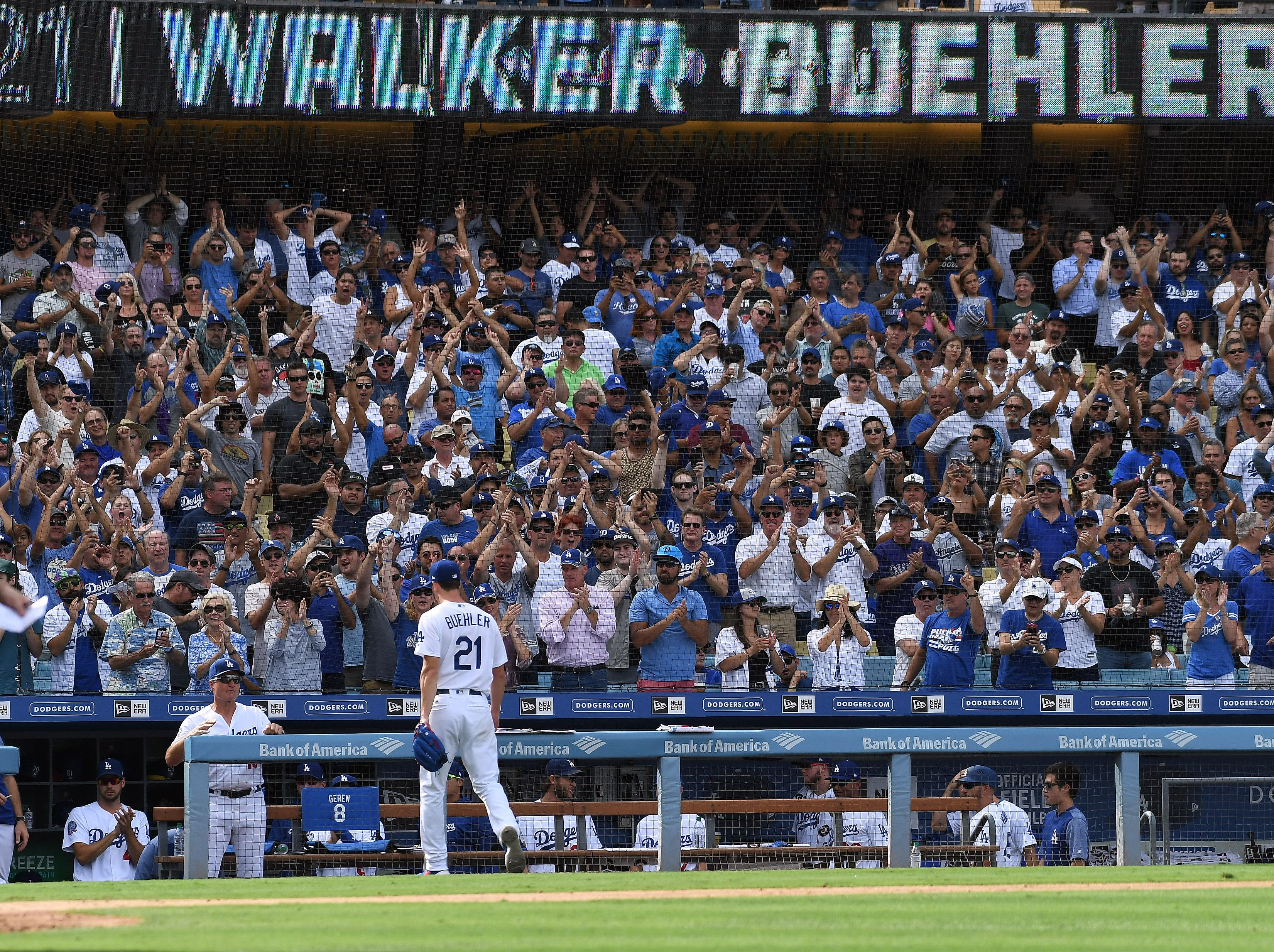 Fans applaud Dodgers pitcher Walker Buehler as he walks off the mound in the seventh inning.