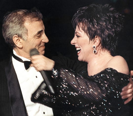 In this Nov.8, 1987 file photo, American singer Liza Minnelli welcomes French singer Charles Aznavour onto the stage at the end of her show at the Lido cabaret in Paris.