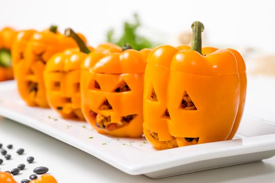 Carve jack o' lantern faces into these stuffed peppers for a healthful Halloween dish.