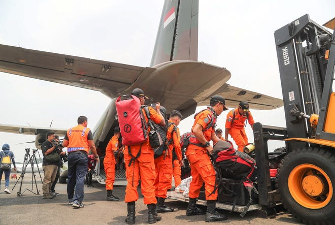 Members of the Indonesian National Search and Rescue Agency prepare their gear inside a military base before being transported to the disaster area after a 7.7 magnitude earthquake that hit Central Sulawesi.
