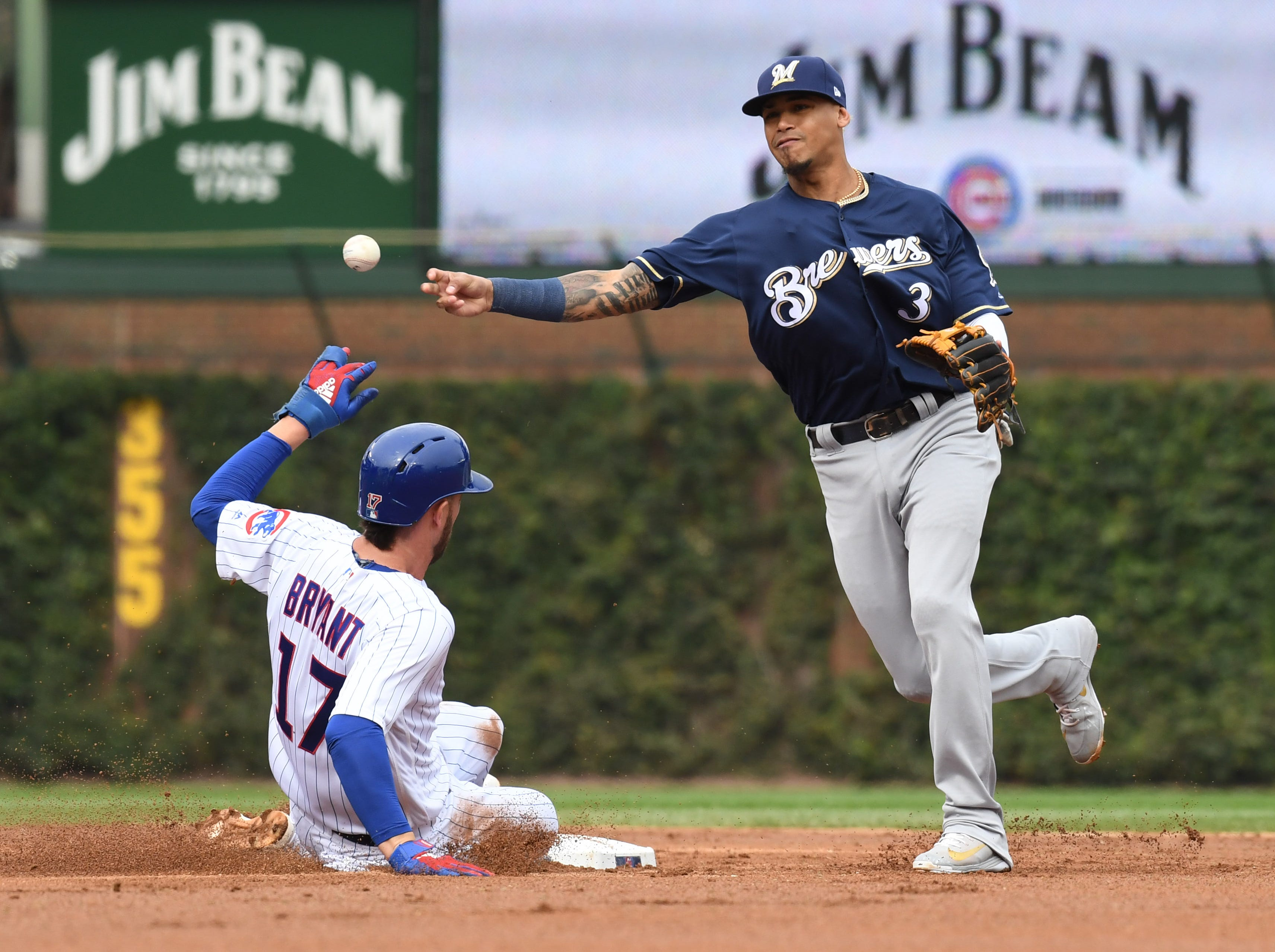 Brewers shortstop Orlando Arcia turns a double play in the second inning as Kris Bryant slides in.