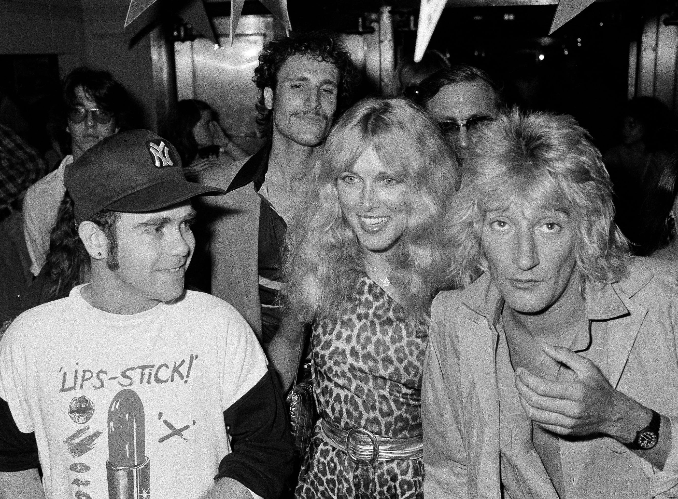 Elton John, left, Alana Hamilton, wife of actor George Hamilton, and rock singer Rod Stewart arrive at Studio 54, July 10, 1978, to celebrate at a party given by RCA Records.