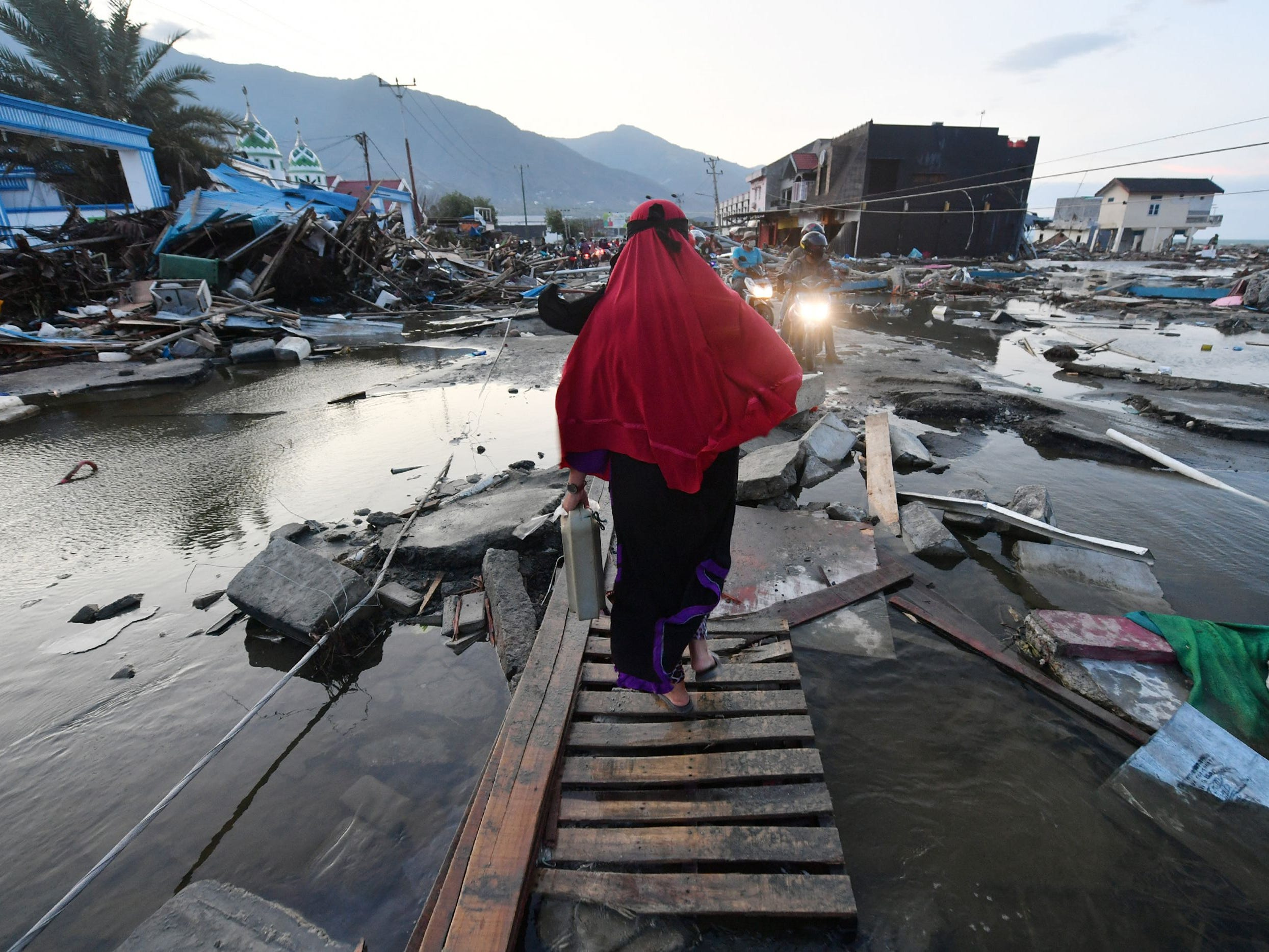 TOPSHOT - A woman walks through a devastated area in Palu, Indonesia's Central Sulawesi on October 1, 2018, after an earthquake and tsunami hit the area on September 28. - Indonesian volunteers began burying bodies in a mass grave with space for more than a thousand people on October 1, victims of a quake-tsunami that devastated swathes of Sulawesi and left authorities struggling to deal with the sheer scale of the disaster.