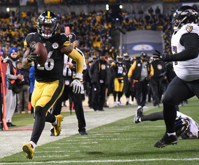 Pittsburgh Steelers running back Le'Veon Bell (26) scores a fourth quarter touchdown as Baltimore Ravens defensive tackle Michael Pierce (97) gives chase at Heinz Field.