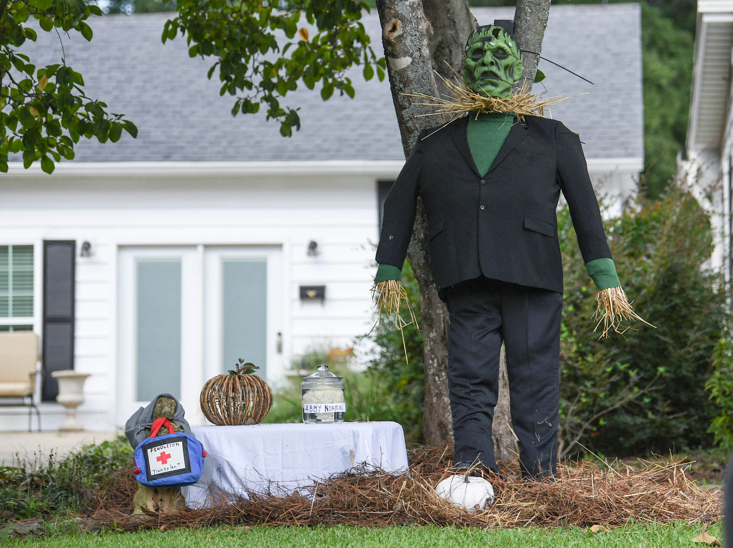 """A Frankenstein with a table with words """"Pendleton transplant"""" is one of many displays in The Pendleton Scarecrow Contest leading up to the 20th Fall Harvest Festival in the village green Saturday, October 6 from 10 a.m. to 5 p.m. The annual contest in Pendleton for businesses, individuals, groups, organizations and churches who create fun not scary Scarecrows. People driving around the downtown square can see different theme scarecrows."""