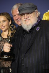 "George R.R. Martin and the cast and crew of ""Game of Thrones"" pose with their awards for Drama Series in the photo room during the 70th Emmy Awards at the Microsoft Theater on Sept. 17."
