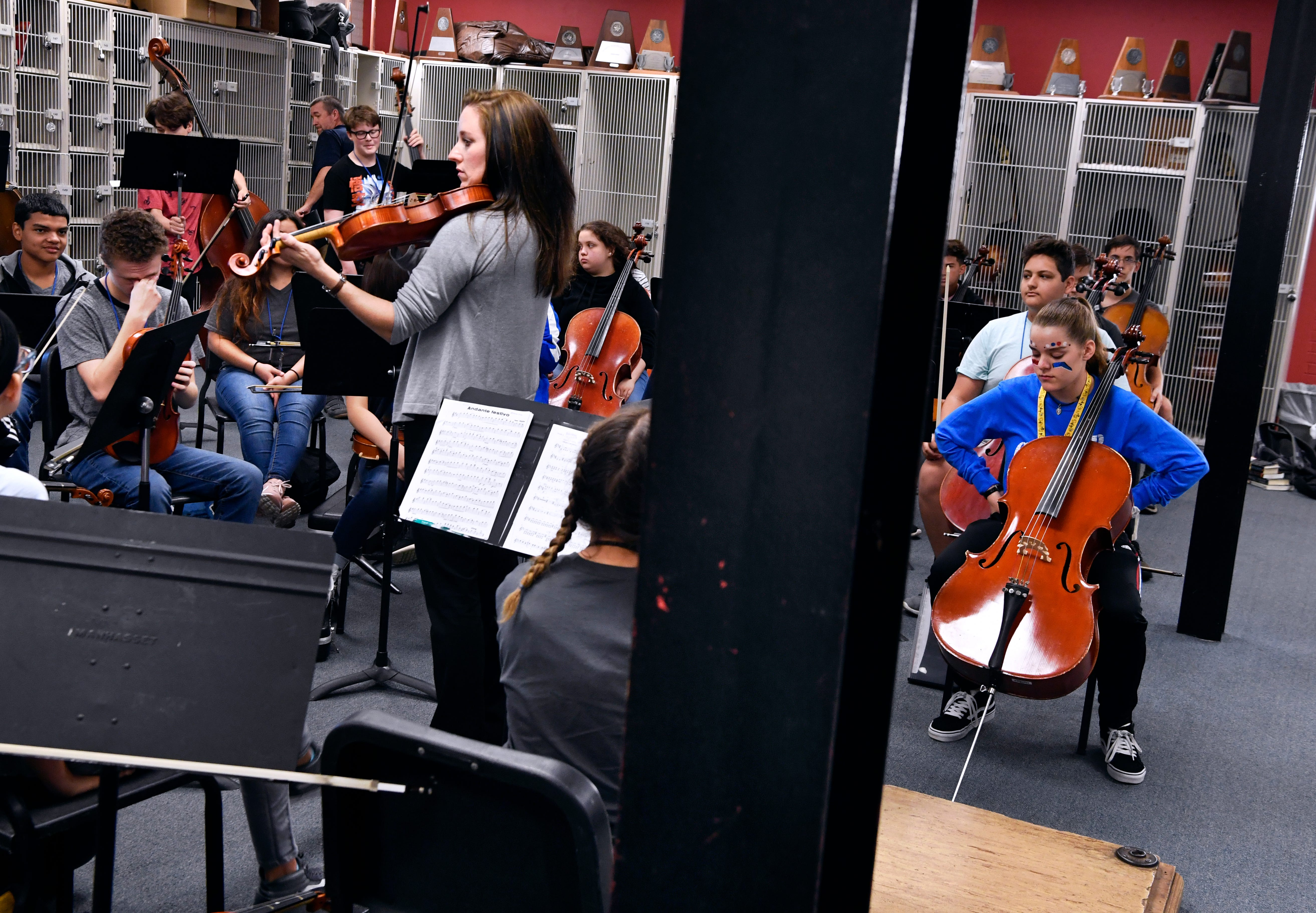 Darcy Radcliffe, the director of orchestra at Cooper and Abilene high schools, leads a rehearsal at Cooper. The twin I-beams supports in the room are just two of the obstacles students have to cope with in class.