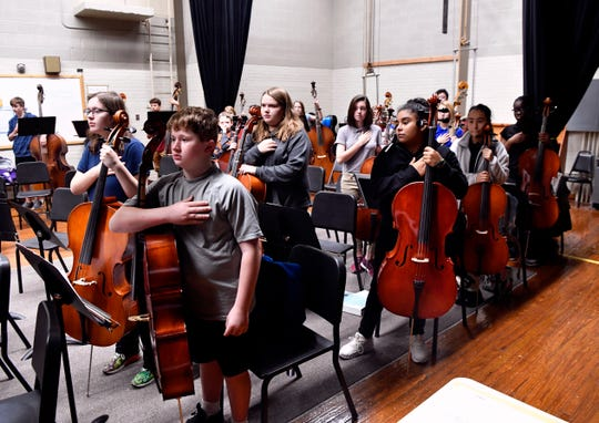 Orchestra students at Madison Middle School stand for the Pledge of Allegiance during rehearsal. The orchestra does not have a rehearsal hall and uses the school auditorium for that purpose.