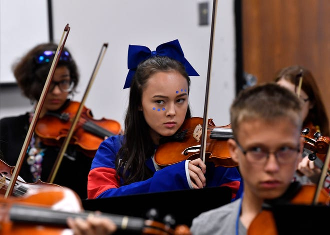 Freshman Triniti Johnson watches her teacher, Darcy Radcliffe, during rehearsal Sept. 27  at Cooper High School. The orchestra room is not designed well enough to accommodate the group, officials say.