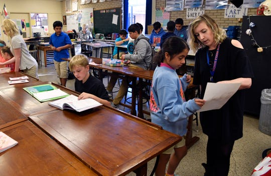 Madison Middle School art teacher Brady Sloane assists a student during class,