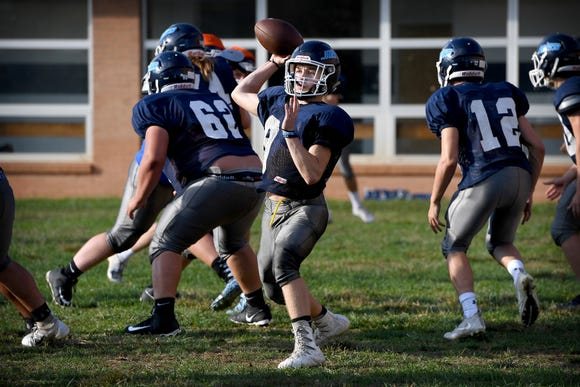 Enka sophomore Jared Smith throws a pass as he runs plays at quarterback during practice at Enka High School on Oct. 1, 2018.