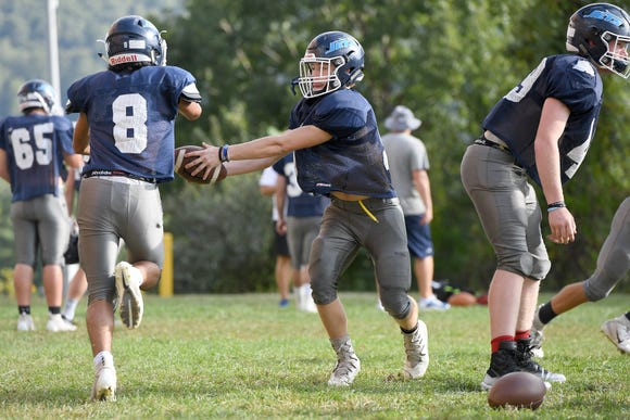 Enka sophomore Jared Smith hands the ball off to junior Shannon Gacusana as he runs plays at quarterback during practice at Enka High School on Oct. 1, 2018.