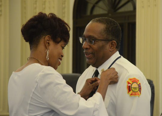 Tamra Flowers, girlfriend of new Battle Creek Fire Chief Brian Sturdivant, pins on his badge after he was sworn into office Tuesday, Oct. 2, 2018.